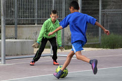 Children play football in the schoolyard Stock Images