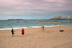 Children play football by the sea in rainy weather royalty free stock images