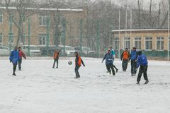 Children play football in the snowy stadium in the winter in the street stock photos