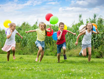 Children play games with ballons. Children laught and play in games with multicolored balloons in leisure park Royalty Free Stock Photography