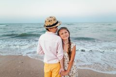 Children play and have fun on the beach.Girl with boy hold hands. Retro style. Children play and have fun on the beach. Loving teens. Romantic story on the stock photography