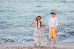 Children play and have fun on the beach. The girl and the boy stand and hold hands. Children play and have fun on the beach. Loving teens. Romantic story on the royalty free stock image