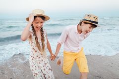 Children play and have fun on the beach. The girl and the guy run away from the waves. Children play and have fun on the beach. Loving teens. Romantic story on royalty free stock image