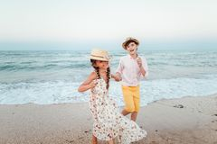 Children play and have fun on the beach. The girl and the guy run away from the waves. Children play and have fun on the beach. Loving teens. Romantic story on stock images