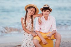 Children play and have fun on the beach. The girl and the guy run away from the wavesThe girl and the boy are sitting on a yellow royalty free stock image
