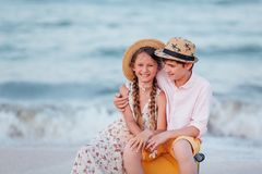 Children play and have fun on the beach. The girl and the guy run away from the wavesThe girl and the boy are sitting on a yellow stock images