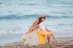 Children play and have fun on the beach. The girl and the guy run away from the wavesThe girl and the boy are sitting on a yellow royalty free stock photography