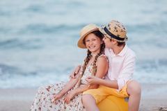 Children play and have fun on the beach. The girl and the guy run away from the wavesThe girl and the boy are sitting on a yellow royalty free stock photos