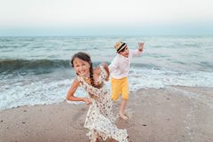 Children play and have fun on the beach. The girl and the guy run away from the waves. Children play and have fun on the beach. Loving teens. Romantic story on stock photography