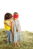 Children play hide and seek. Little boy girl Tying with a scarf eyes. Children play in the hayloft hide-and-seek -Isolated on white background Stock Photos