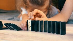 Children play at home in self-isolation during quarantine: build a chain of falling dominoes.