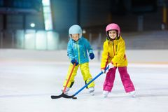 Children play ice hockey on indoor rink. Healthy winter sport for kids. Boy and girl with hockey sticks hitting puck. Child. Skating. Little kid on sports stock images