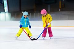 Children play ice hockey. Kids winter sport. Children play ice hockey on indoor rink. Healthy winter sport for kids. Boy and girl with hockey sticks hitting stock photography
