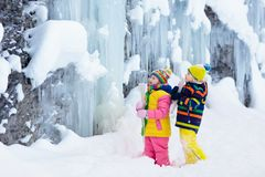 Children play with icicle in snow. Kids winter fun. Children play with icicle in snow. Kids lick icicles at frozen mountain waterfall on family Christmas stock images