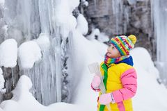 Children play with icicle in snow. Kids winter fun. Children play with icicle in snow. Kids lick icicles at frozen mountain waterfall on family Christmas stock photos
