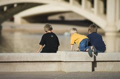 Children Play at Inner City Lake. Three young children enjoy a summer day by exploring a local man made lake in the middle of a large metropolitan city Stock Photography