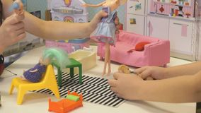 Children play in kindergarten indoors. Children in kindergarten indoors. Two little unidentified girls play with dolls with colored hair in dollhouse. Close-up stock video footage