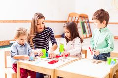 Children play with kinetic sand. Babysitter and children play with kinetic sand in the daycare Royalty Free Stock Photo