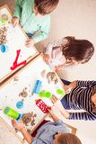 Children play with kinetic sand. Teacher and kids play with creative kinetic sand on the table Royalty Free Stock Photo