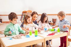 Children play with kinetic sand. Teacher and kids play with creative kinetic sand on the table Stock Photography