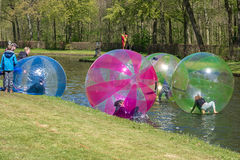 Children play in large plastic balls on the pond of the park Stock Photography