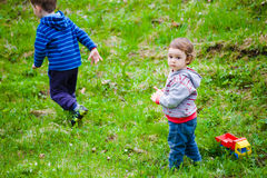 Children play on the lawn. Two kids playing on a green lawn toys Royalty Free Stock Photography