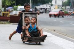 Children play with a makeshift wooden trolley at the Liwasang Bonifacio in front of the Manila Central Post Office in Lawton, royalty free stock image