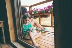 The children play a mobile phone. stock photos