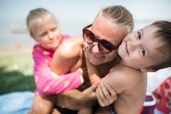 children play with mother on the beach stock photos