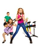 Children play musical instruments as rock group. Four children playing on musical instruments together as rock group and girl singing as vocalist in front on Royalty Free Stock Photo