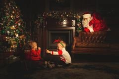 Children play near the Christmas tree. The real Santa Claus is watching them
