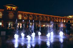 Children play with night fountains in the city of Lodz. Beautiful evening
