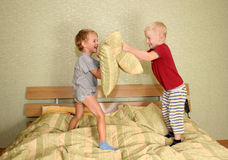 Children play with pillows. Happy children play with pillows Royalty Free Stock Photography
