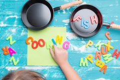 Children play plastic letters to combinations word COOKING . Royalty Free Stock Photos