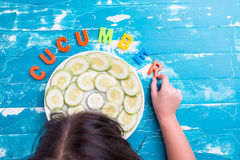 Children play plastic letters to combinations word Cucumber . Stock Images