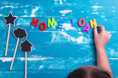 Children play plastic letters to combinations word Home Loan . Stock Image