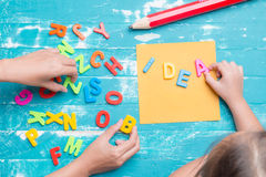 Children play plastic letters to combinations word IDEA . Royalty Free Stock Images