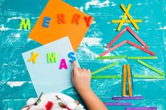 Children play plastic letters to combinations word MERRY X MAS Royalty Free Stock Photos