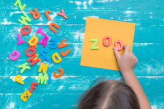 Children play plastic letters to combinations word ZOO . Royalty Free Stock Images