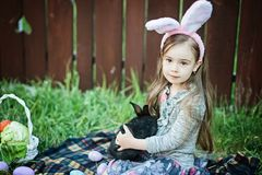 Children play with real rabbit. Laughing child at Easter egg hunt with white pet bunny. Little toddler girl playing with animal in Stock Photo
