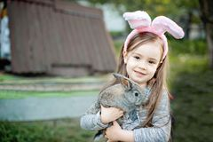 Children play with real rabbit. Laughing child at Easter egg hunt with white pet bunny. Little toddler girl playing with animal in. The garden. Girl feeding Stock Image