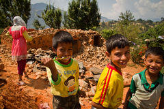 Children play in the rubble of their former devastated home afte Stock Image