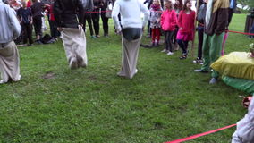 Children play sack race in city park with big people audience stock video