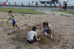 Children play with sand on the seashore in SHENZHEN Stock Photo