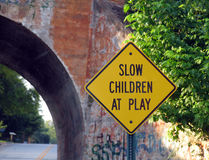 Children At Play sign. Slow Children at Play sign with railroad bridge in the background royalty free stock images