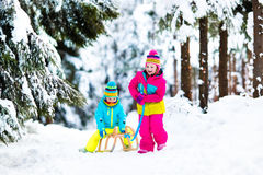 Children play in snow on sleigh in winter park Royalty Free Stock Photography