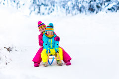 Children play in snow on sleigh in winter park Royalty Free Stock Images
