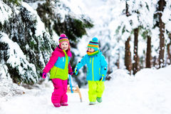 Children play in snow on sleigh in winter park Stock Photography
