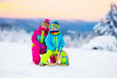 Children play in snow on sleigh in winter park Stock Image