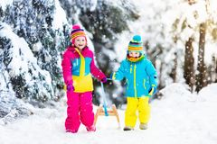 Children play in snow on sleigh in winter park Stock Photo